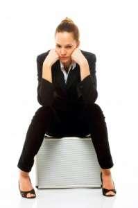 Молодая женщина сидит на чемодане