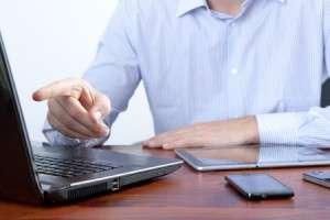 Человек указывает на экран ноутбука